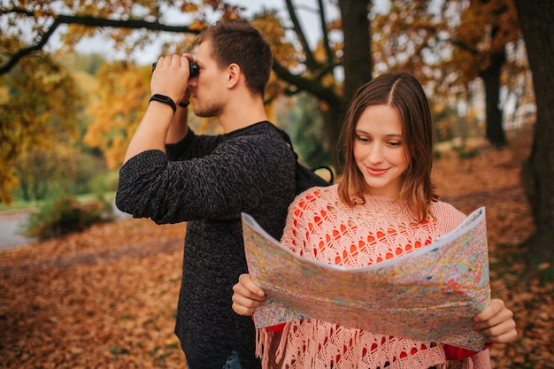 一緒に旅行する美しいカップル。彼女は地図を持って勉強しています。彼は一方向に双眼鏡で見ています。女性のポーズ。