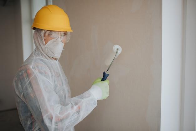 ビルダーは建設現場で働いています。ペイントローラーと労働者。彼は顔の保護スーツとマスクを着ています