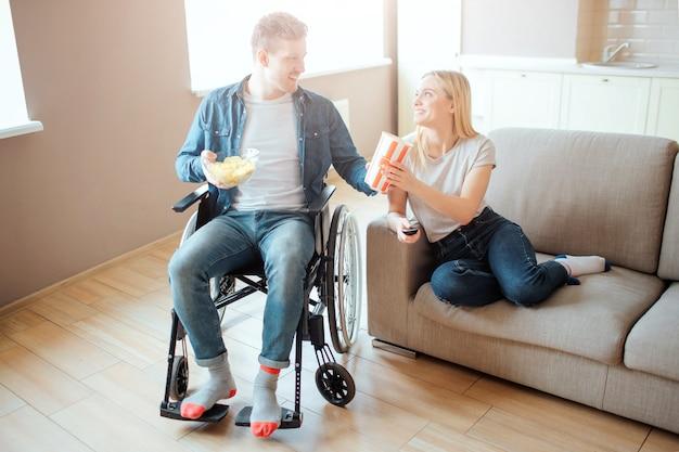 部屋で一緒に陽気なカップル。障害のある男が車椅子に座り、女性を見る。彼女はソファに座り、男に微笑む。排他性。