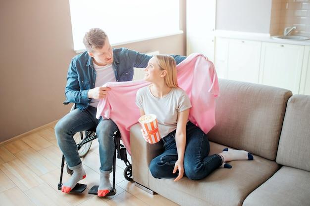 障害と包括性を持つ人はガールフレンドの世話をします。彼は車椅子に座って、彼女の肩に毛布を置きます。彼女は振り返って微笑んでいます。特別なニーズを持つ人。