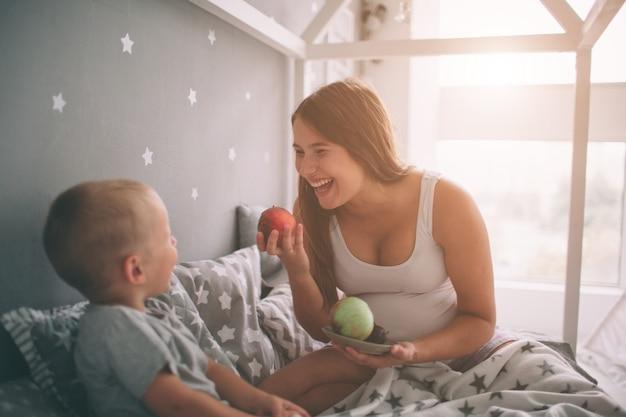 妊娠中の母親と小さな男の子の息子は、午前中に自宅のベッドでリンゴと桃を食べています。寝室でのカジュアルなライフスタイル。