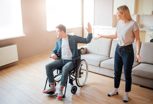 車椅子の若い男は、ガールフレンドと主張します。障害と包括性。特別なニーズを持つ人。動揺して不幸な若い女性。
