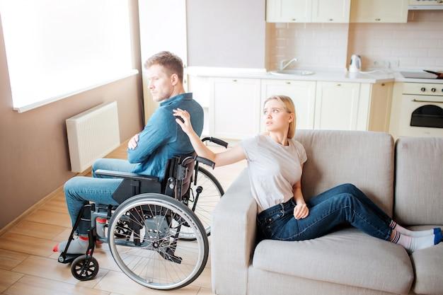 特別なニーズを持つ若い男は女性と背中合わせに車椅子に座っています。彼女は彼の肩に手で触れ、彼を見ます。動揺して不幸なカップル。