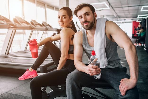 スポーツベンチに座ってポーズ美しいカップルのクローズアップ。また、彼らはボトルから水を飲んでおり、激しい運動の後に休息しています。