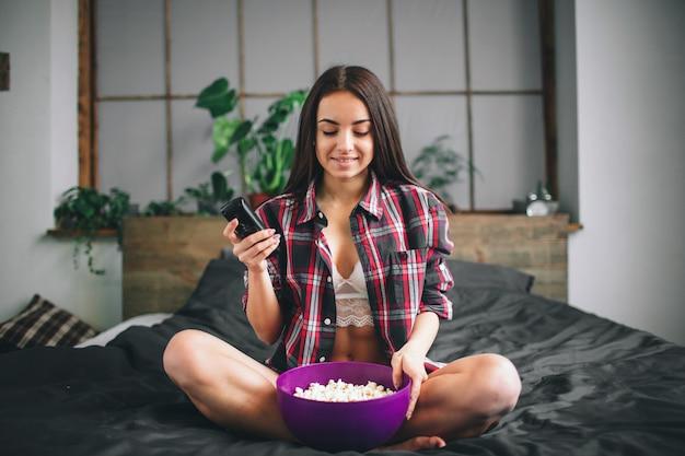 笑っている面白い映画を見ている女性。テレビを見て美しい少女