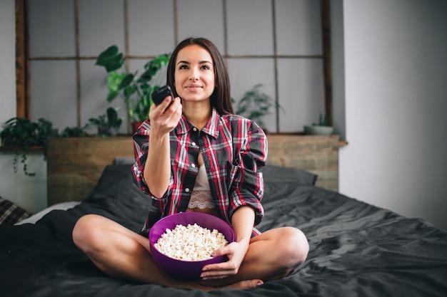 Женщина смотрит смешной фильм смеется. красивая девушка смотрит телевизор