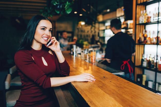Привлекательная брюнетка девушка сидит в клубе возле барной стойки и разговаривает по телефону. она улыбается. бармен стоит недалеко от нее и разговаривает с каким-то парнем.