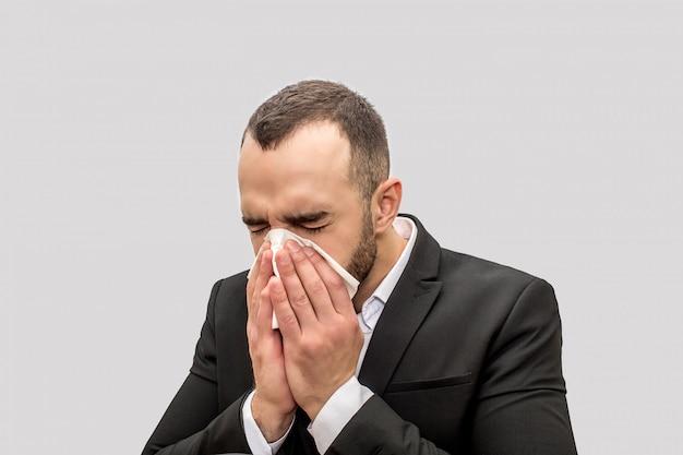 Молодой человек чихает в белую ткань. он держит глаза закрытыми. молодой человек болен.
