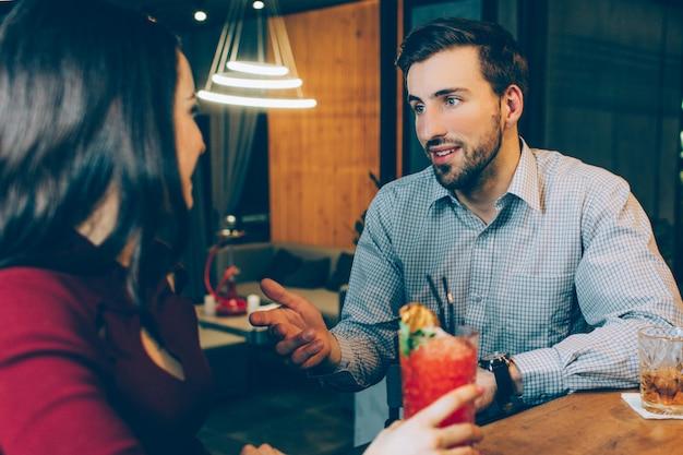 バーに座って女性と話している男性の素敵な写真。彼は見栄えがよく、体格が良い。彼女は右手でカクテルのグラスを持っています。