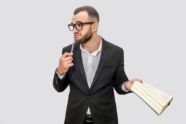 メガネとスーツの若い男が立っています。彼は唇の近くにペンを持っています。別の手に大きな本があります。