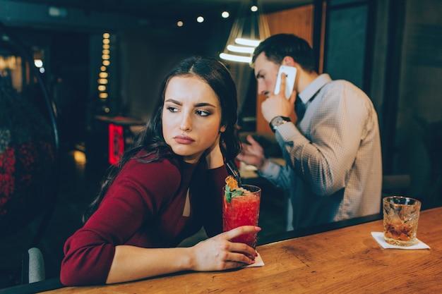 右を見ている少女の悲しい写真。男は電話に応答していて、彼女と時間を過ごしていないので、彼女は悲しいです。彼女は気分がよくありません。