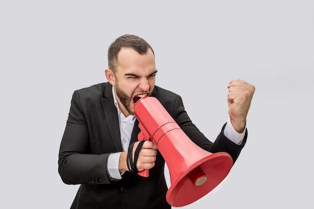 怒って怒っている若者が赤いメガホンに叫びます。彼は片手でそれを保持し、別の手で拳を見せます。脅威のように見えます。