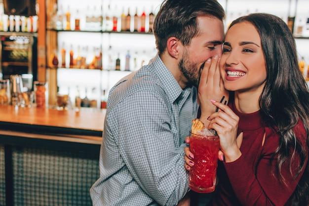 Красивые люди сидят очень близко друг к другу в баре. он что-то шепчет ей на ухо, а она улыбается и смеется. также девушка держит бокал красного коктейля.