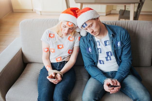 。若い男と女はソーシャルメディア中毒です。クリスマスのコンセプト。ソファの上の疲れたカップル。