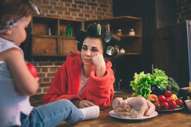Подчеркнула мама дома. молодая мать с маленьким ребенком в домашней кухне. женщина делает много задач, а ухаживает за ребенком
