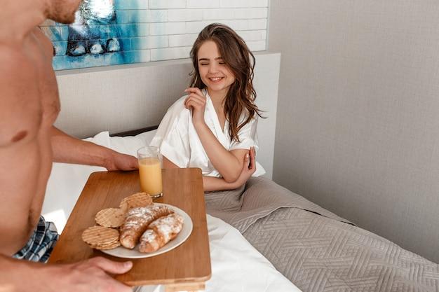 ベッドで若いカップル。幸せな美しい女性が目を覚ます、おいしいクロワッサンとジュースを食べる準備ができて