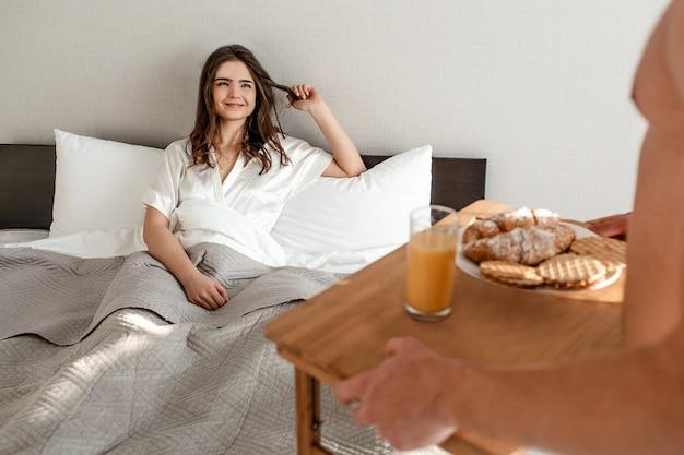ベッドで若いカップル。幸せな美しい空腹の女性は、朝のロマンチックな朝食を待っています。