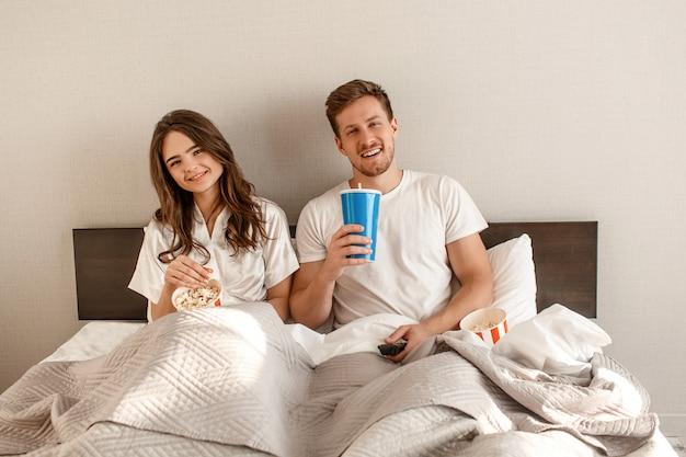 ベッドで若いカップル。笑顔の美しい男と女はポップコーンを食べて、寝室で一緒にテレビを見ています