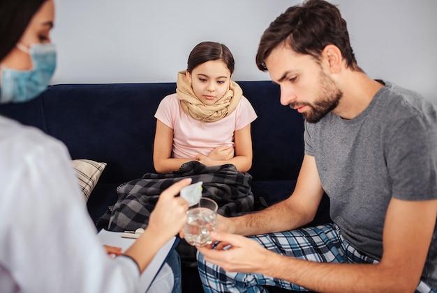 小さな女の子はソファに座っています。彼女の足と喉は覆われています。彼女は、医者がどのように粉末薬をコップ一杯の水に注ぐかを見る。若い男が助けます。彼らは集中して見える。