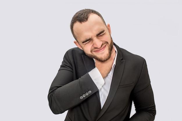 Молодой человек в костюме страдает от боли в горле. он держит руку на шее и сжимается. парень держит глаза закрытыми.
