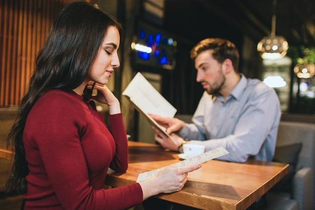 レストランでボーイフレンドと一緒に座っている見事な女の子をよく見てください。どちらもメニューを探しています。彼らはいくつかの食べ物や飲み物を味わいたい。