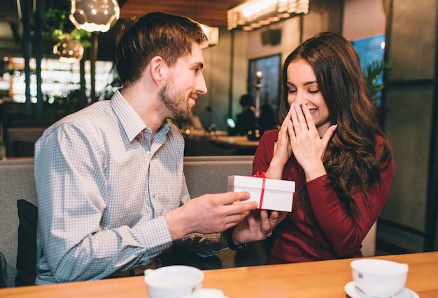 男は彼のガールフレンドに白い箱に贈り物を与えています。彼女はそれを期待していなかった。彼は愛する女性を幸せにするのが好きです。
