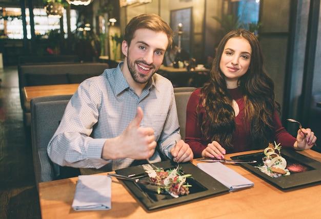 いくつかの食べ物がテーブルに座っている男女の広告写真。彼らはカメラを見て笑っています。男は彼の大きな親指を見せています。