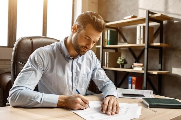 Молодой красивый бизнесмен сидя и писать на таблице в его собственном офисе. он поставил подпись на документах. рабочее время. солнечный свет из окна.