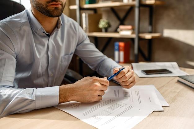 彼自身のオフィスで若いハンサムな実業家のビューをカットします。彼はペンを手に持っています。テーブルの上の文書。署名を入れます。忙しい。
