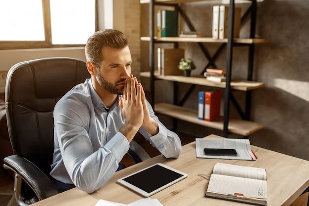 Молодой красивый продуманный бизнесмен сидеть за столом в своем собственном офисе. он держит руки в молитвенном посте. мышление. дневной свет. время работы в офисе.