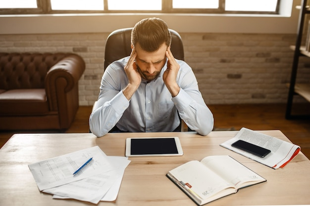 Молодой красивый продуманный бизнесмен работают в своем собственном офисе. он сидит за столом и держится руками за голову. парень смотри вниз.
