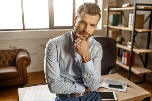 若いハンサムな実業家はテーブルに立って、彼自身のオフィスでカメラにポーズします。彼はあごに手をつないでまっすぐ見ます。ハンサムで自信がある。
