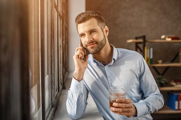 若いハンサムな実業家は窓に立って、彼自身のオフィスで電話で話します。彼はウイスキーを手に持って外を見ます。自信を持って素敵な若い男。