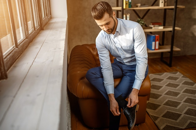 若いハンサムな実業家はソファに座って、彼自身のオフィスで靴のひもを結ぶ。ウィンドウの横にある自信を持って男。輝く太陽の光。