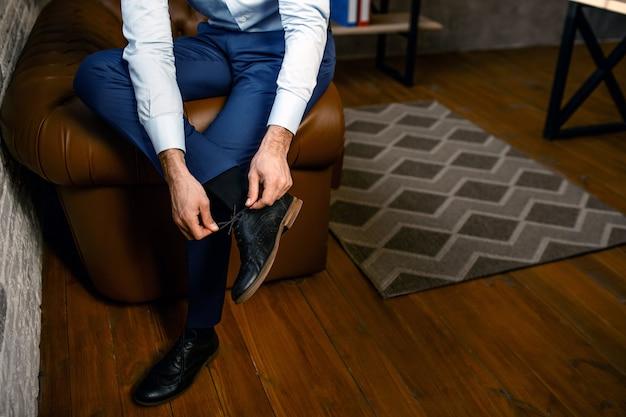 彼自身のオフィスで若いハンサムな実業家のビューをカットします。彼はもう片方の足を持ち、靴ひもを結びます。忙しい。
