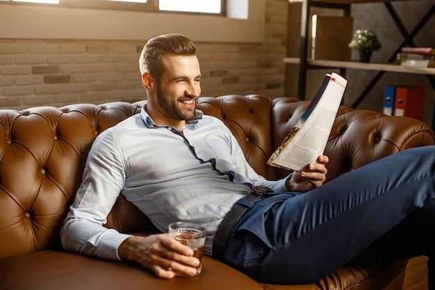 若いハンサムな実業家はソファに座って、彼自身のオフィスで読んでください。彼はグラスにウイスキーを手に持って微笑んでいます。ポジティブで幸せ。ハンサム。