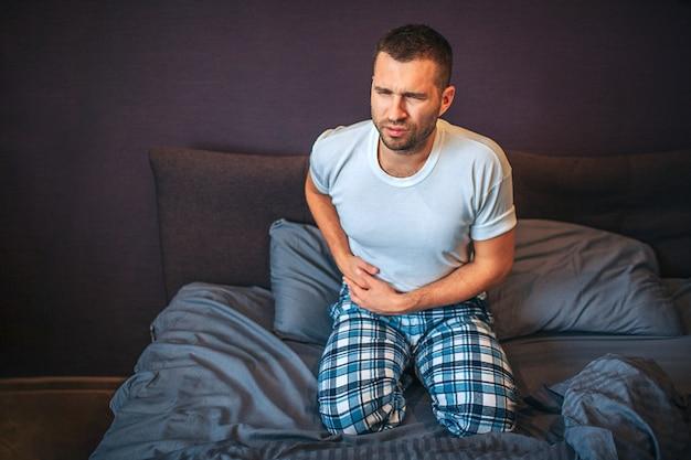Молодой человек стоит на коленях на кровати и страдает от болей в области червеобразного отростка. он держит руки там. парень сжимается. он носит пижаму.