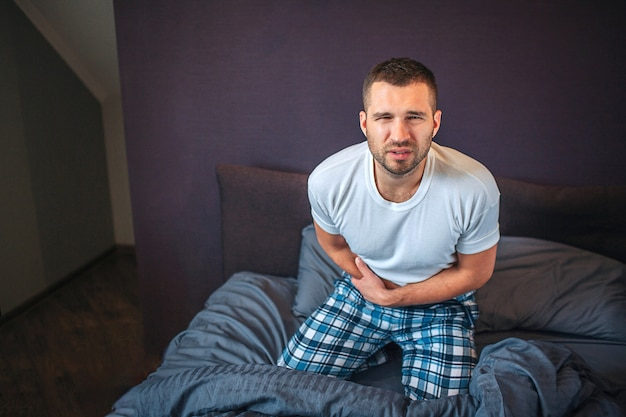 Молодой и светлый человек стоит на коленях на кровати и смотрит на камеру. он сжимается. парень держит руки на области приложения. он чувствует боль. парень страдает.