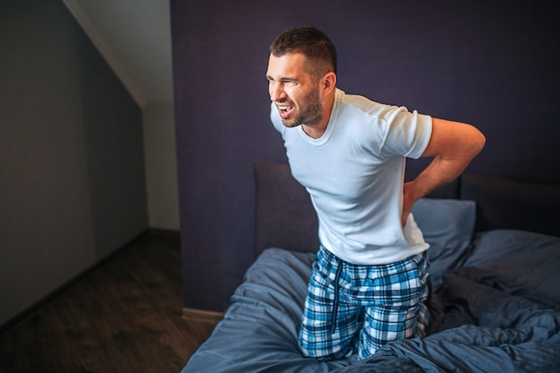若い男が叫んでいます。彼は背中を握り、楽しみにしている。彼はパジャマを着ています。男は苦しんでいます。痛みが強い。彼は寝室にいます。