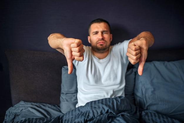 不幸で負の若い男はベッドに座って、カメラに見えます。彼は大きな親指を下げます。男は怒っています。彼は寝室にいます。