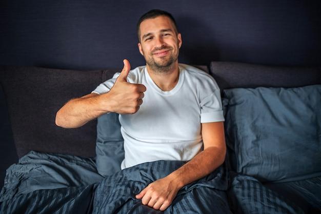 ベッドの上に座って肯定的な若い男とカメラに見えます。彼は笑って、大きな親指を立てます。男は寝室にいます。