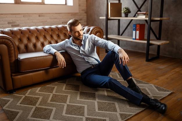若いハンサムな実業家は床に座って、彼自身のオフィスでポーズします。彼は自信を持ってまっすぐに見えます。セクシーな若い男はソファーにもたれます。