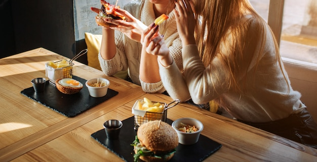 食卓とゴシップで座っている若い女性のカットビュー。彼らは食事を手に持っています。