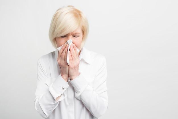 病気の老婦人はハンカチでくしゃみをしています。彼女は風邪をひいたようです。彼女は良くなるためにいくらかの治療をしなければなりません。閉じる。白で隔離