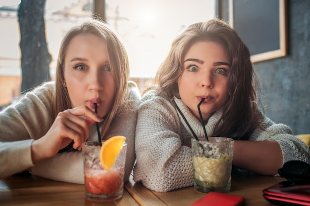 若い女性はテーブルに座って、ストローでカクテルを飲みます。彼らはまっすぐに見えます。モデルはおかしく見えます。彼らはテーブルの内側に座っています。