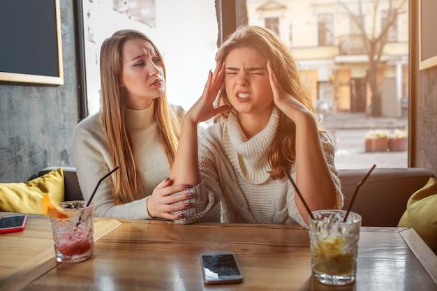 Сердитый молодой человек держатся за руки на голову. у нее головная боль. ее друг сидит рядом с ней и пытается утешить. брюнетка раздражена.
