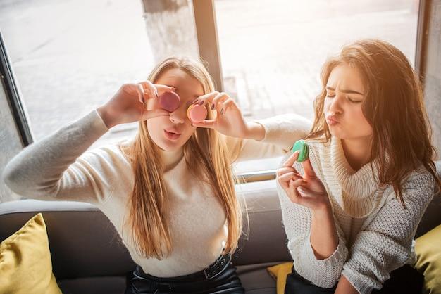 遊び心のある若い女性はマカロンを食べて目を覆っています。彼らは一緒に楽しんでいます。