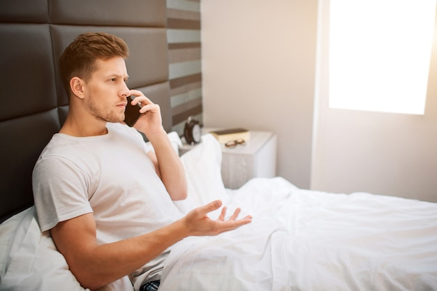 今朝ベッドで若い男。深刻な男性モデルは部屋のベッドに座って電話で話します。彼は白い毛布で覆われていました。明け。早朝。目が覚めた。