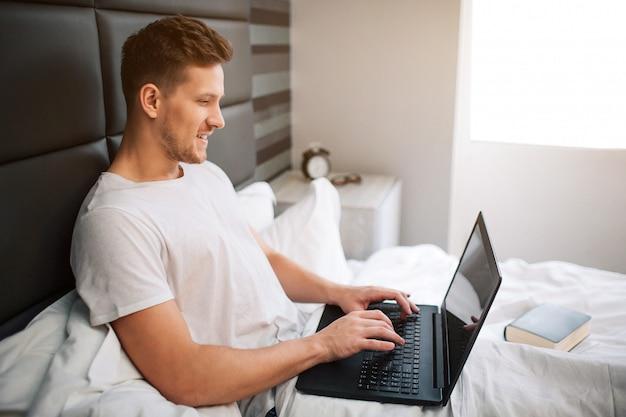 陽気な素敵な若い男は、早朝のベッドで働きます。男はラップトップを保持し、キーボードで入力します。笑顔で前向き。明け。