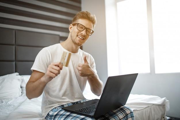 陽気な正の若い男が今朝ベッドの端に座っています。彼はカメラを見て笑います。男はクレジットカードを持ち、大きな親指を表示します。膝の上のラップトップ。